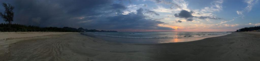Západ slnka na piesočnatej pláži, rozhovor s cestovateľom