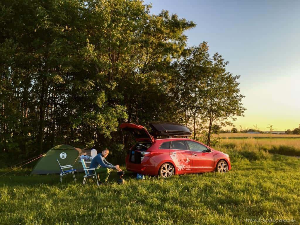 Kemping v prírode so stanom a autom pri západe slnka, Vista travellers