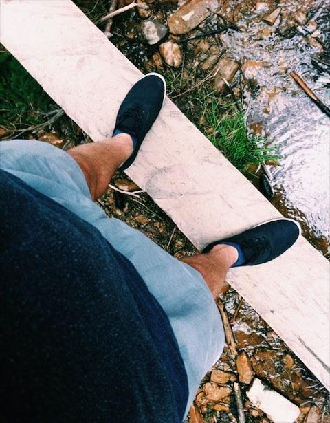 Chlap stojaci na tenkej doske nad malým potokom