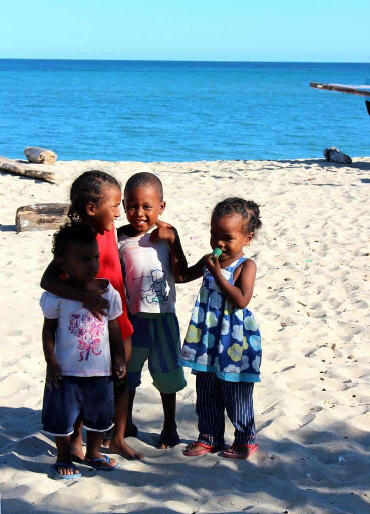 Malé černošské deti na piesočnatej pláži Anakao na ostrove Nosy Ve