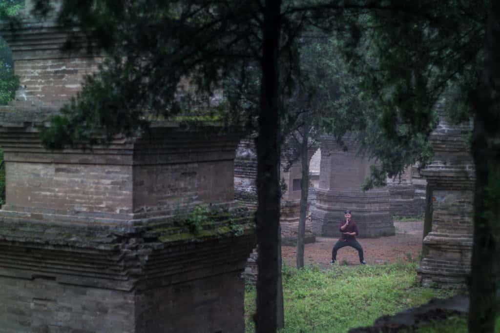 Trénujúci šaolín medzi starobylými budovami chrámu