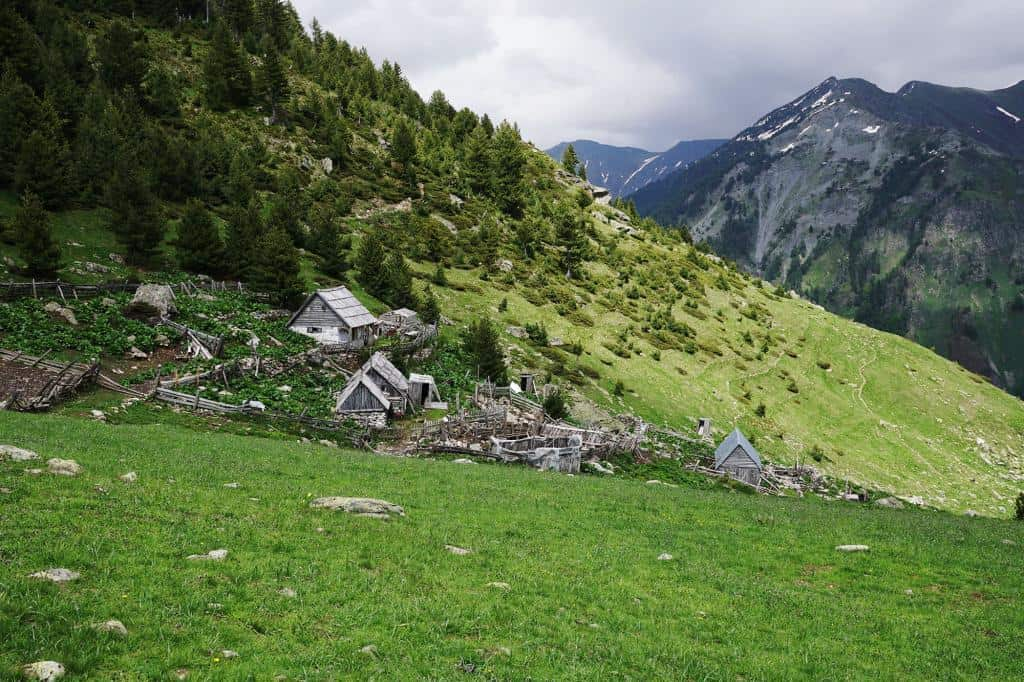 Staré drevené chatky na úbočí hory v Albánsku