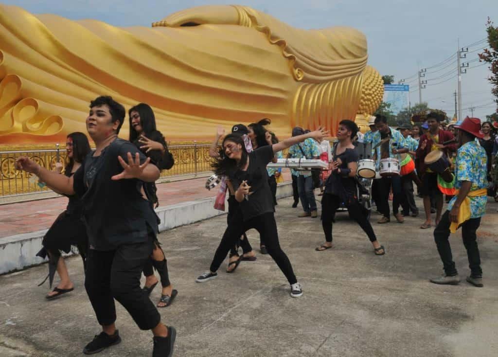 Tancujúci obyvatelia Thajska pri ležiacej soche Buddhu