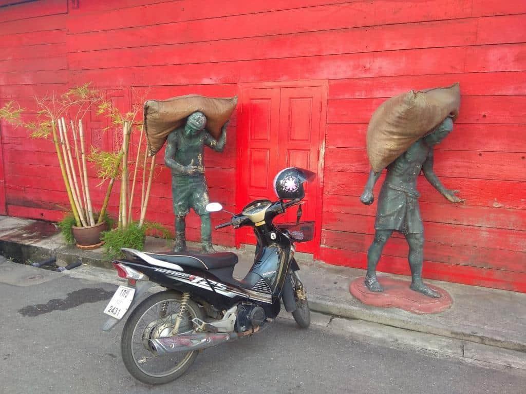 Motorka a sochy pracujúcich ľudí v meste Songkhla
